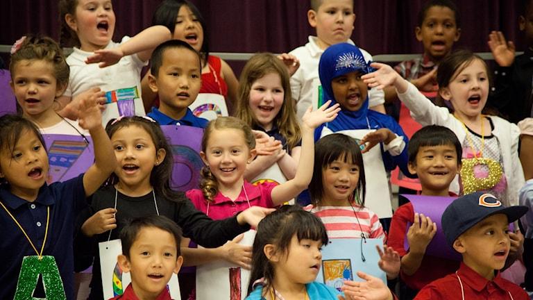 Barn som sjunger och viftar med händer och armar.