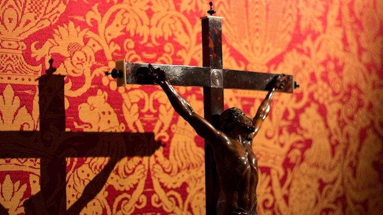 Ett crucifix med Jesus som skuggar sig mot en mönstrad tapet.