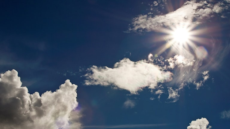 Solen strålar fram bakom molnen på en blå himmel.