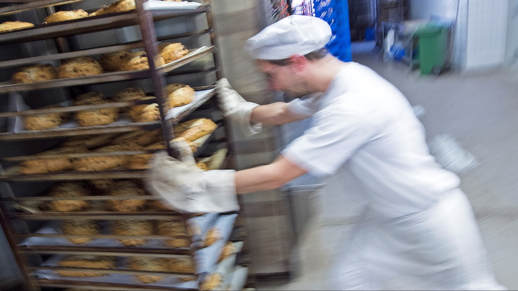 En bagare skjuter en vagn full med plåtar med bröd på framför sig.