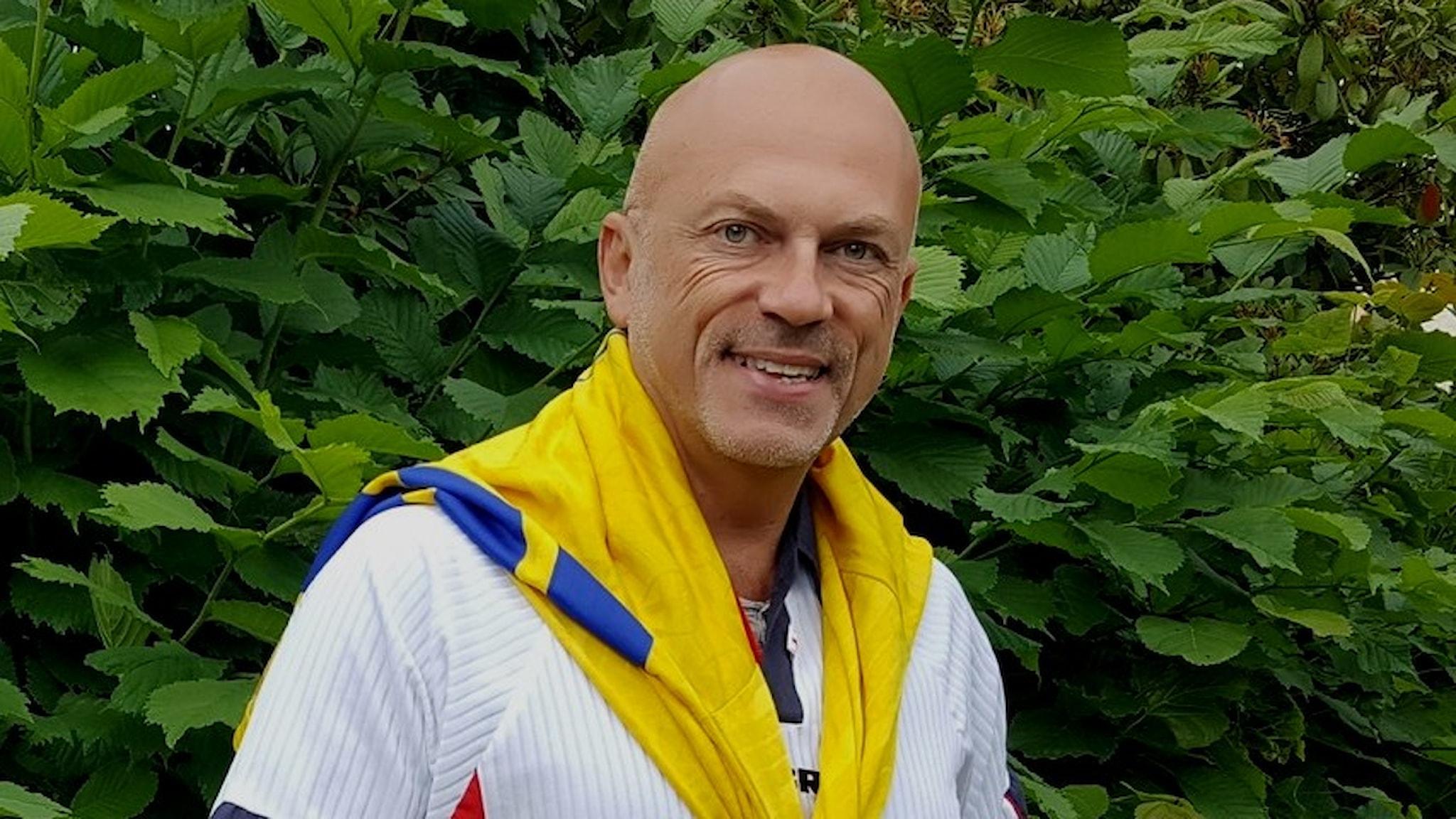Keith Foster står framför gröna buskar. Han har på sig Storbritanniens fotbollslandslags matchtröja. Över axlarna har han det svenska fotbollslandslagets tröja.