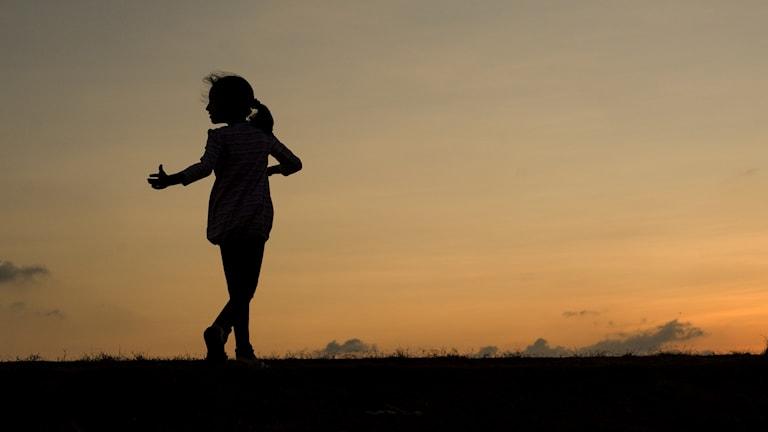 Siluetten av en dansande flicka mot en kvällshimmel.