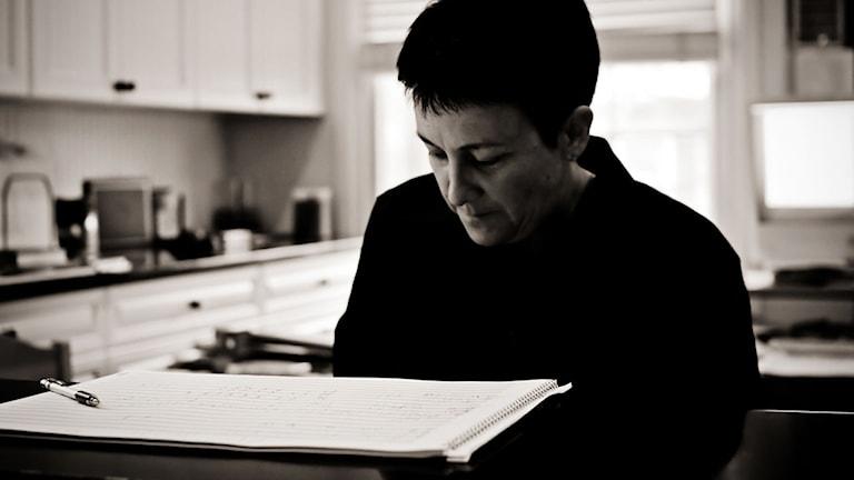 Tonsättaren Jennifer Higdon sitter i ett kök med ett notblock framför sig på bordet.