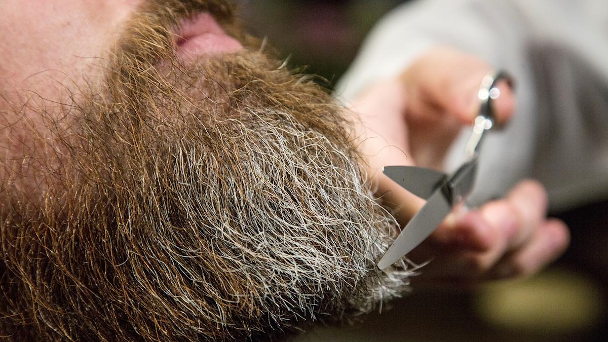 En man får sitt skägg klippt och ansat av en barberare.