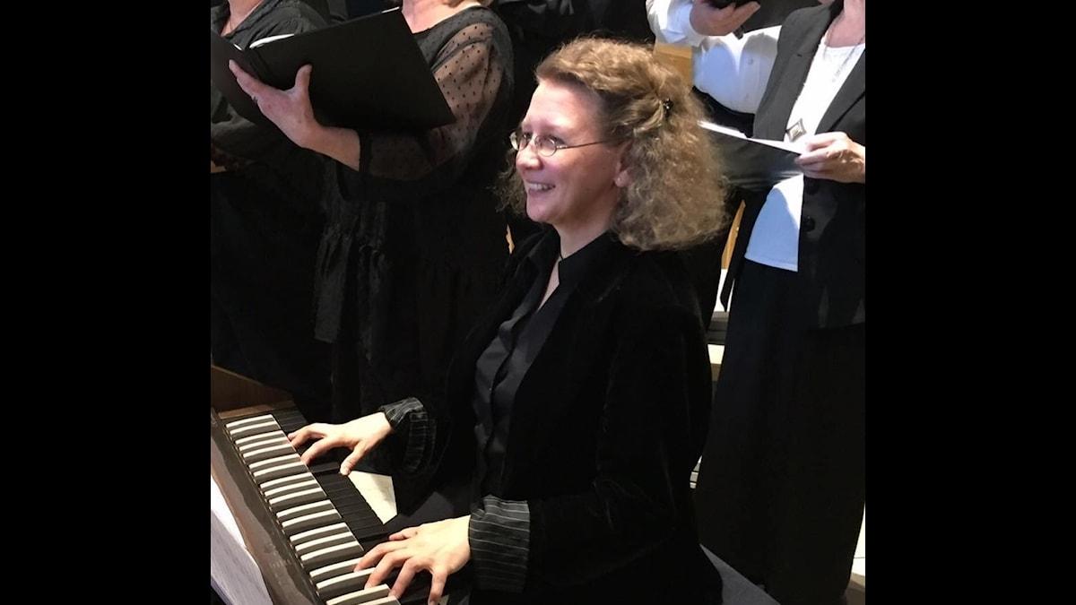 Mirella Sarp sitter och spelar på en elorgel bredvid en sjungande kör.