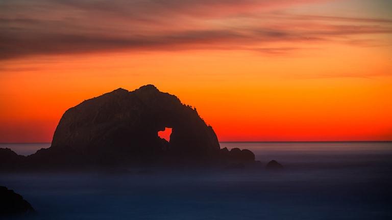 Klippa i havet med hjärtformat hål i solnedgång.