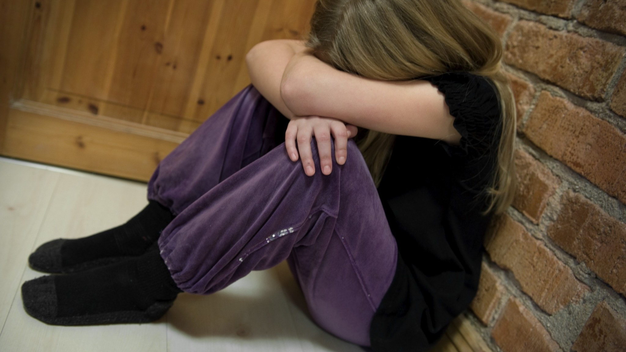 En tjej sitter på golvet med huvudet gömt i knät.