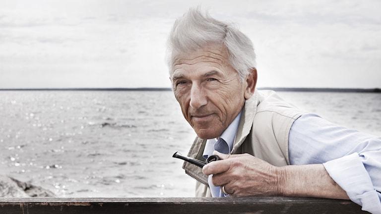 Författaren Theodor Kallifatides sitter vid havet och håller en pipa i sin ena hand.