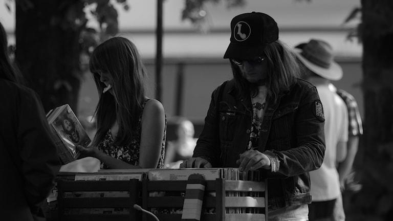 En kvinna och en man letar LP-skivor i en back på en loppmarknad.