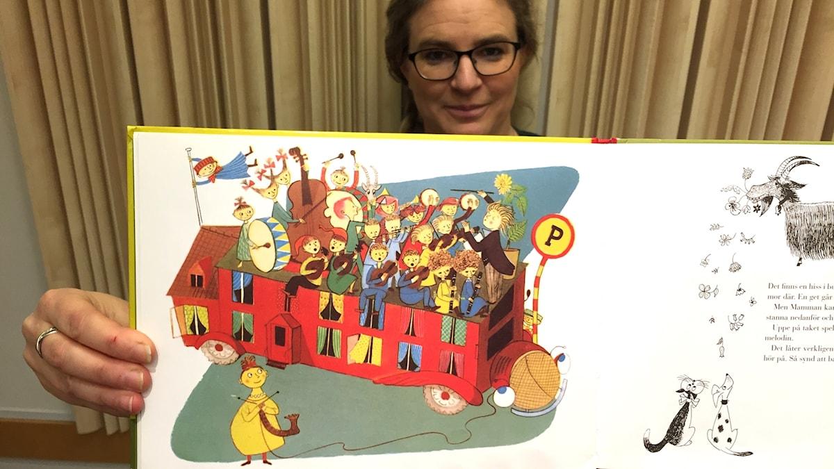 Pernilla Eskilsdotter håller upp boken Musikbussen av Lennart Hellsing.