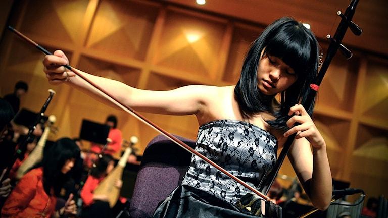 Ungkvinna spelar på det kinesiska instrumentet Erhu.