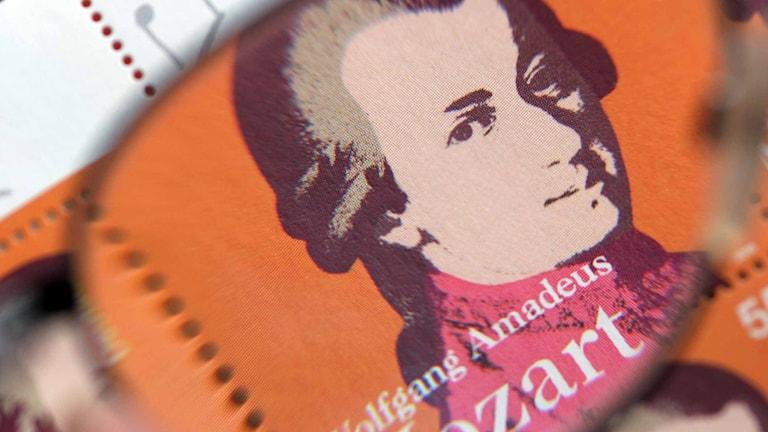 Frimärke på Wolfgang Amadeus Mozart sett genom ett par glasögon.