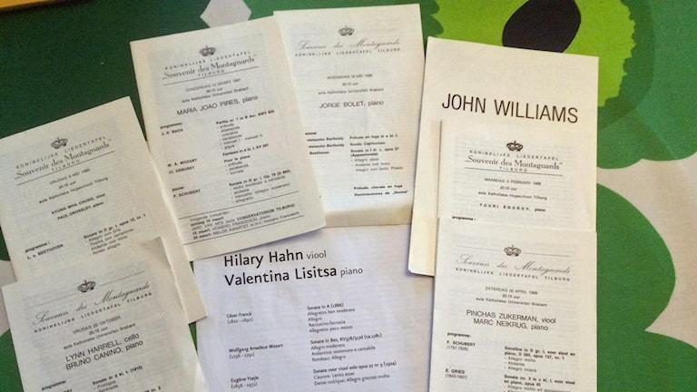 Programblad från konserter som ligger upplagda på en grön duk. Musikernamn på programbladens framsidor, bl.a. Hilary Hahn, Valentina Lisitsa.