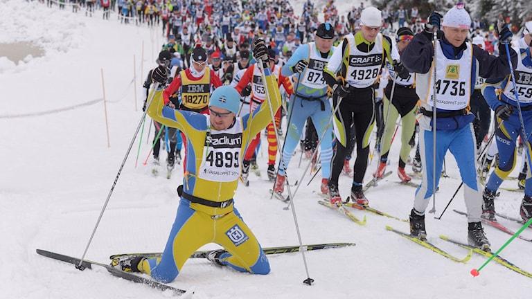 Johan Hägg från Skövde får problem i Vasaloppets första backe och faller ner på knä. Bakom honom kommer tusentals and´ra skidåkare.