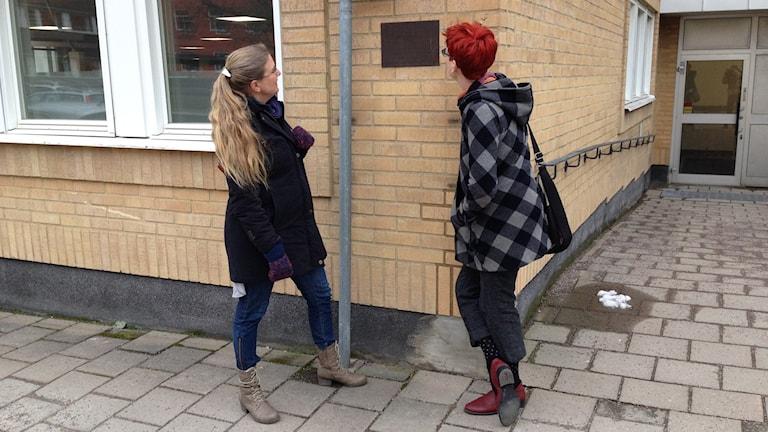 Pernilla Eskilsdotter och Tuva Klinthäll kollar på en metallskylt på väggen på etthus på Nygatan 16 i Växjö. Skylten berättar om tonsättaren Karl-Birger Blomdahl födelshem.