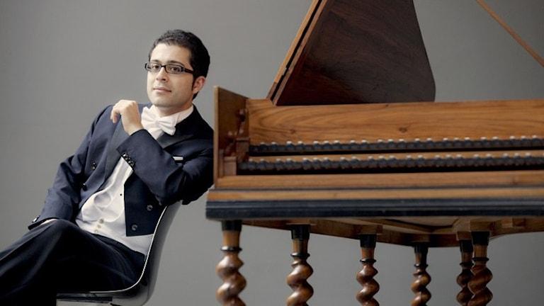 Cembalisten Mahan Esfahani sitter på en stol iklädd frack. Han lutar sig mot sitt instrument.