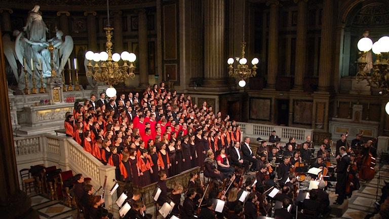 Kör och orkester som sjunger och spelar Stabat mater i en kyrka.