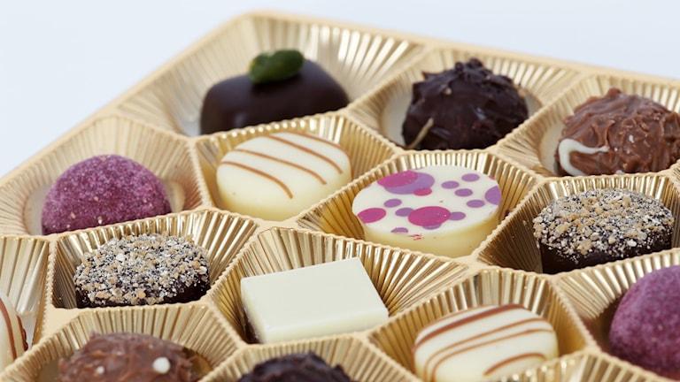 Chokladpraliner i olika färger och former ligger i chokladask.