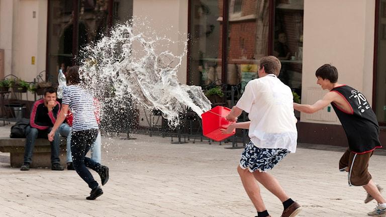 Två pojkar kastar en hink med vatten över en flicka som försöker fly undan vätan.