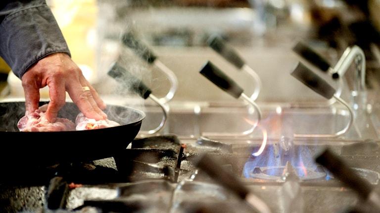 Köttbitar steks i en stekpanna på en gasspis.