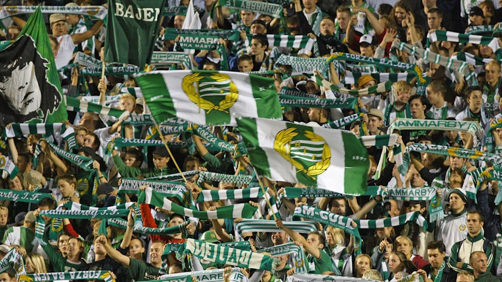 Läktare med Hammarbys fans som sjunger och viftar med flaggor och halsdukar.