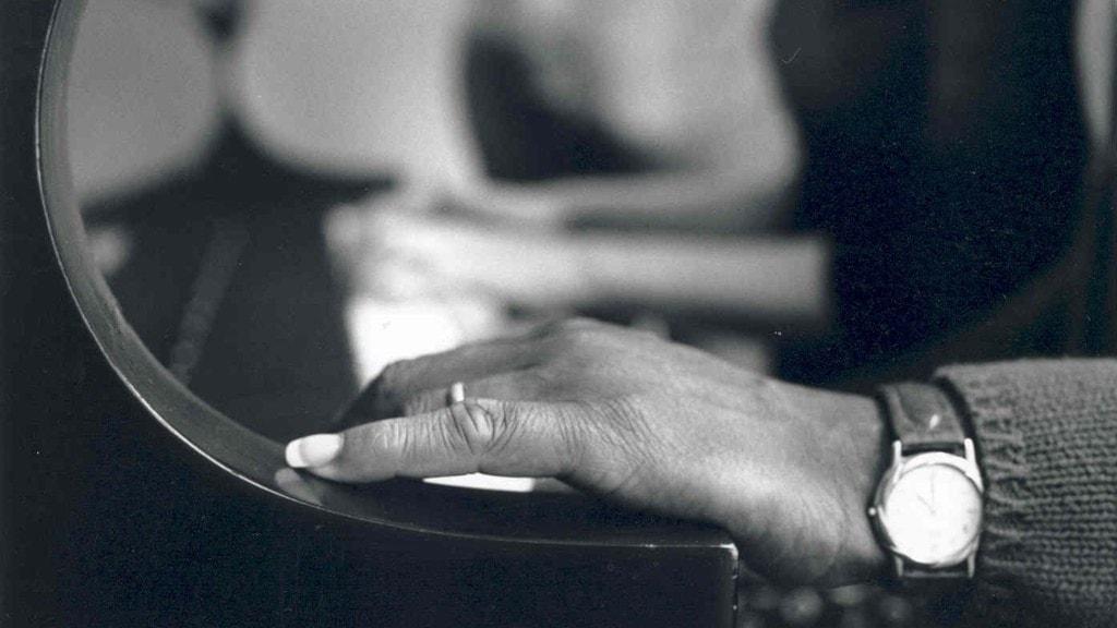 Hand som vilar på kanten vid sidan av tangenterna på ett piano. I bakgrunden syns två händer som spelar längre bort på tangenterna.
