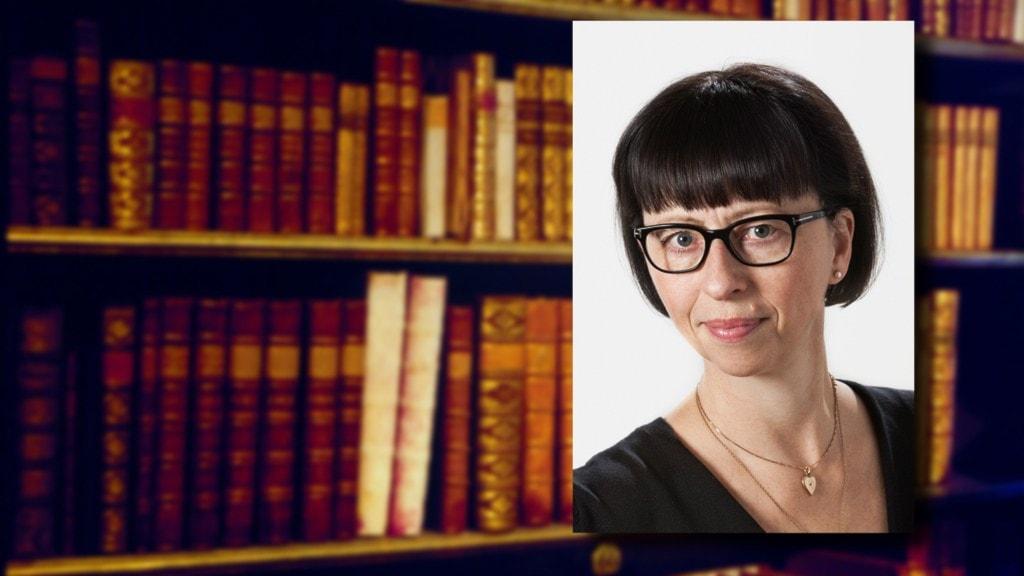 Orkesterbibliotekarien Inger Marie Garcia de Presno. I bakgrunden gamla böcker i en bokhylla.