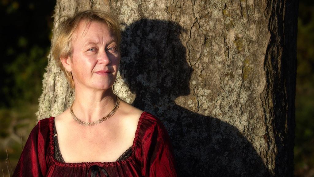 Tonsättaren och sångaren Karin Höghielm framför ett träd.