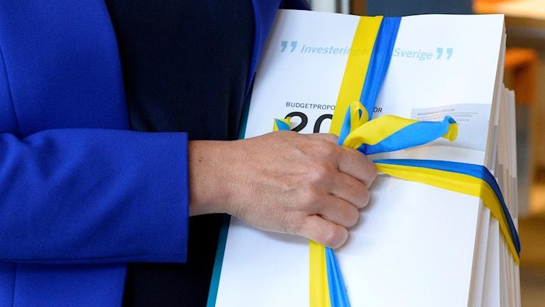 Finansminister Magdalena Anderssons högra hand håller i budgetdokumenten.