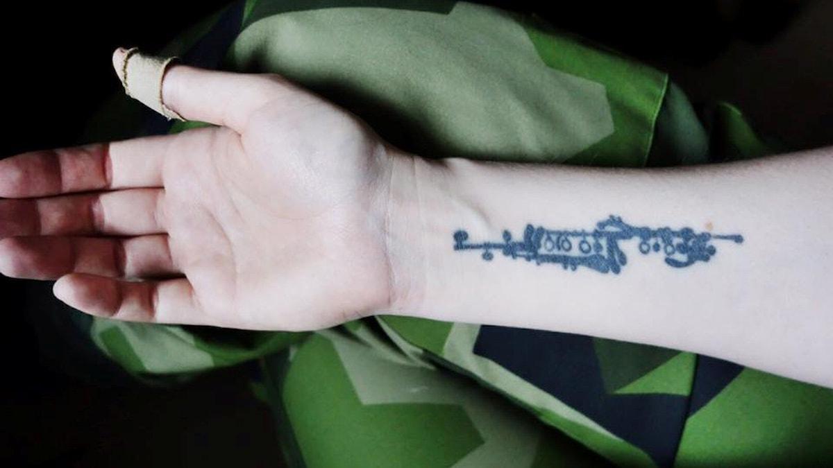 En tatuering föreställande mekaniken på en klarinett pryder Astrids högra underarm.