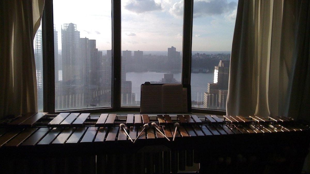 En marimba står framför ett fönster med vy över skyline i storstad.