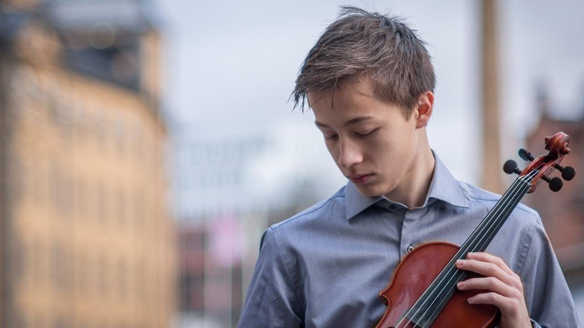Violinisten Johan Dalene tittar ner på sin fiol.