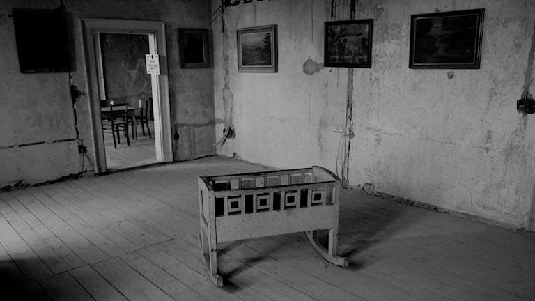 En tom vagga står på golvet i ett tomt rum.