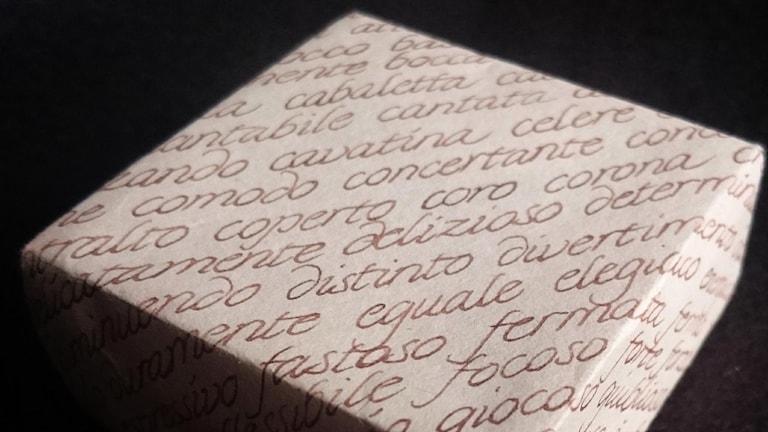 En ask vikt av kalligrafipapper med italienska musiktermer i skönskrift.