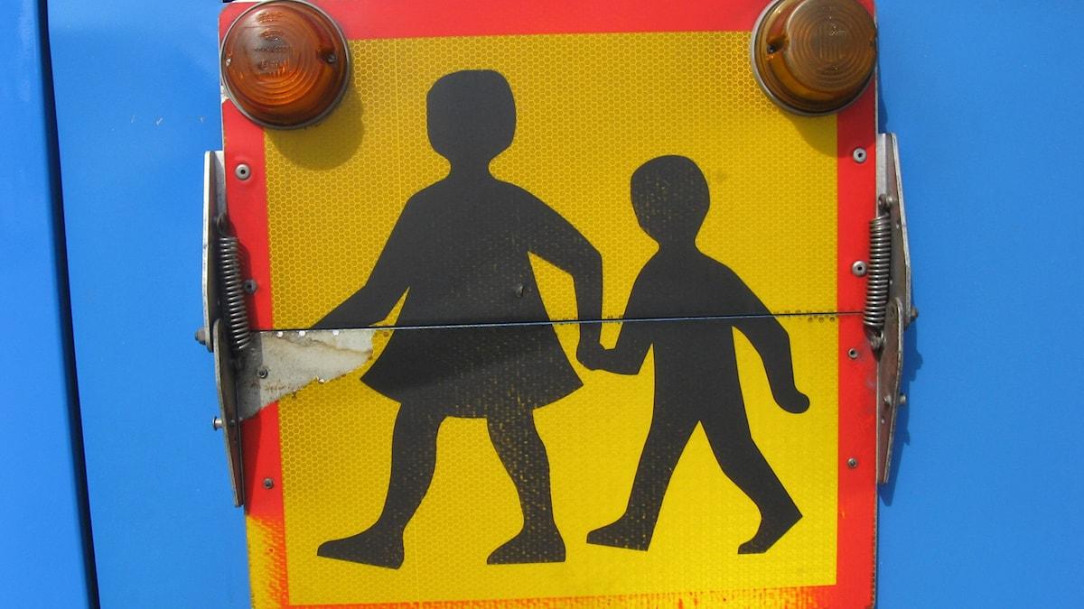 Skolbuss-skylt på blå skolbuss.