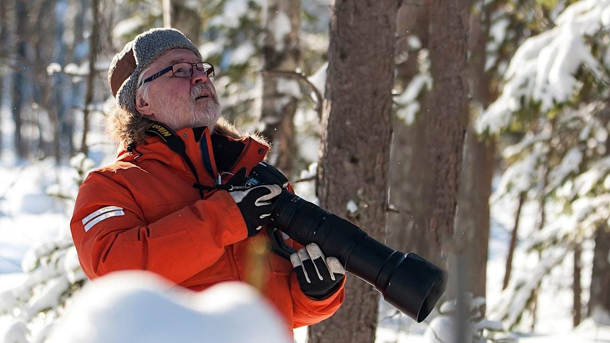 Ulf Jonsson med kameran i högsta hugg spanar efter fåglar att fotografera.