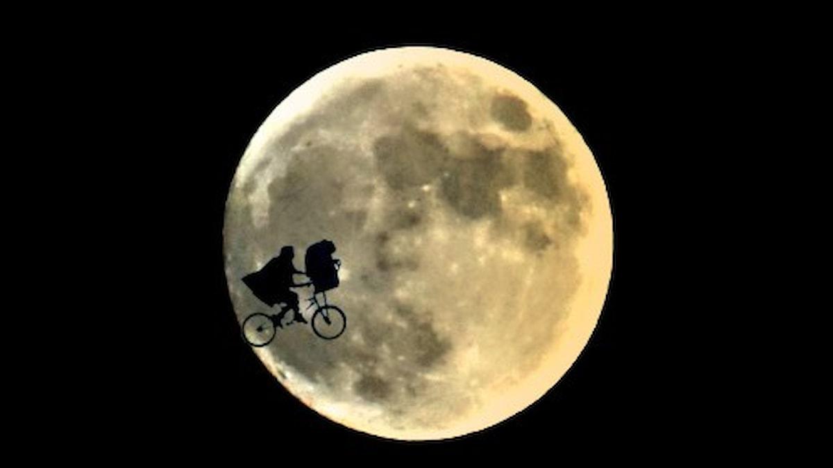 BMX-cykel med E.T. i cýkelkorgen framför en helmåne.