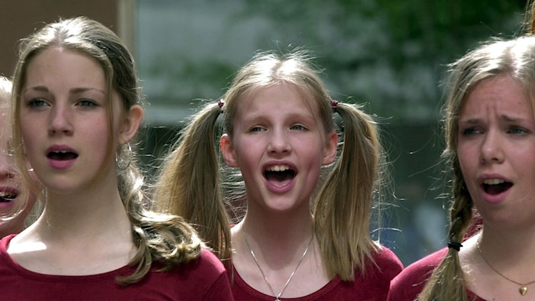 Tre flickor ur Adolf Fredriks flickkör sjunger.