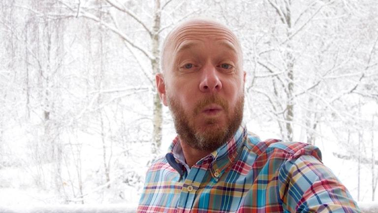 Jörgen Eriksson visslar framför en snöig bakgrund.