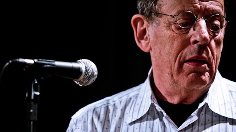 Närbild på kompositören Philip Glass som vänder sig bort från en mikrofon.