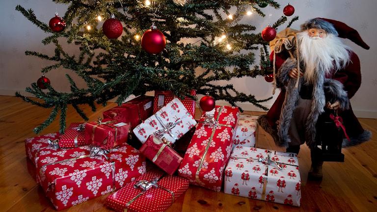 Julklappar och en prydnadstomte under en julgran.
