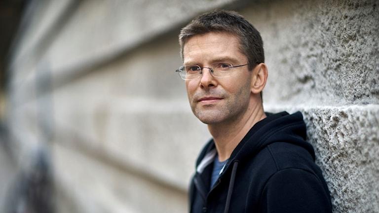 Albert Schnelzer har kort snaggat hår och glasögon. Han bär en blå huvtröja och står framför en betongvägg.