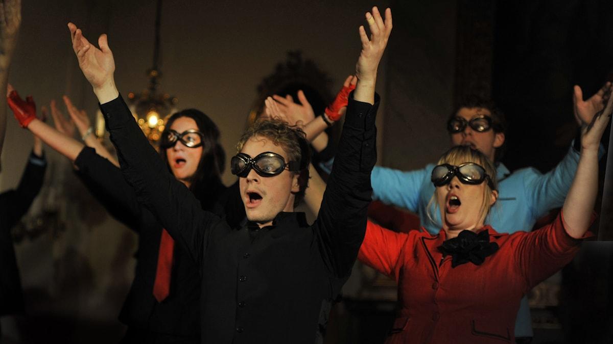 Vokalensemblen Voces Nordicae iklädda gammaldags flygarglasögon sträcker armarna i luften och sjunger.