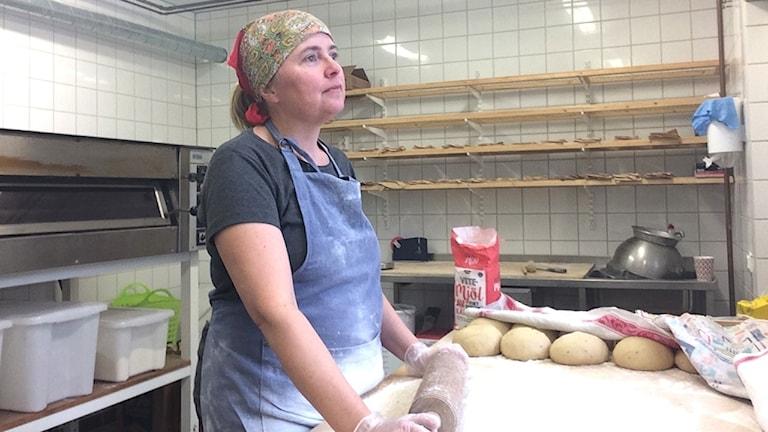 Maria Svensson står och kavlar tunnbröd.