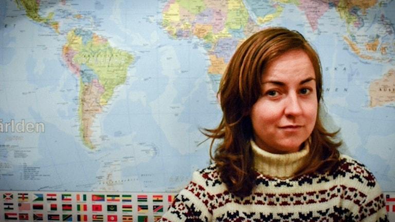 Irina Carlén står framför en världskarta.