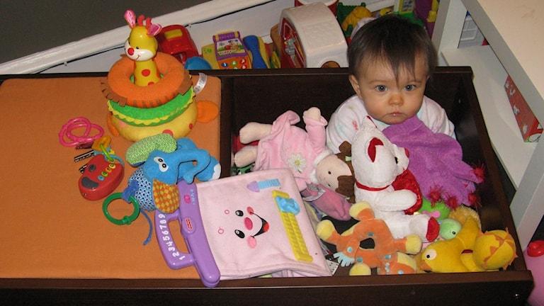 Barn som sitter i en leksakslåda full med gosedjur.