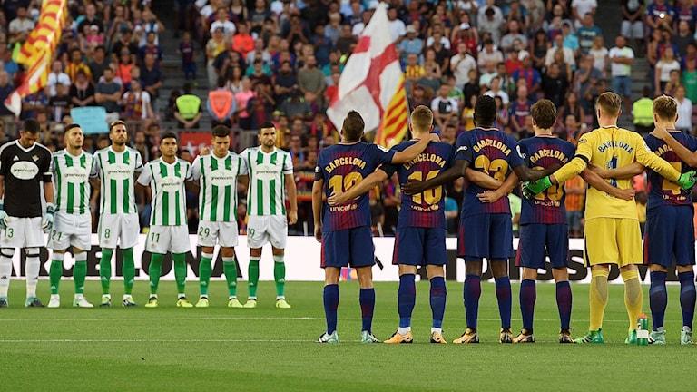 Fotbollslagen Real Betis och Barcelona står uppradade under den tysta minuten innan avspark på Camp Nou.
