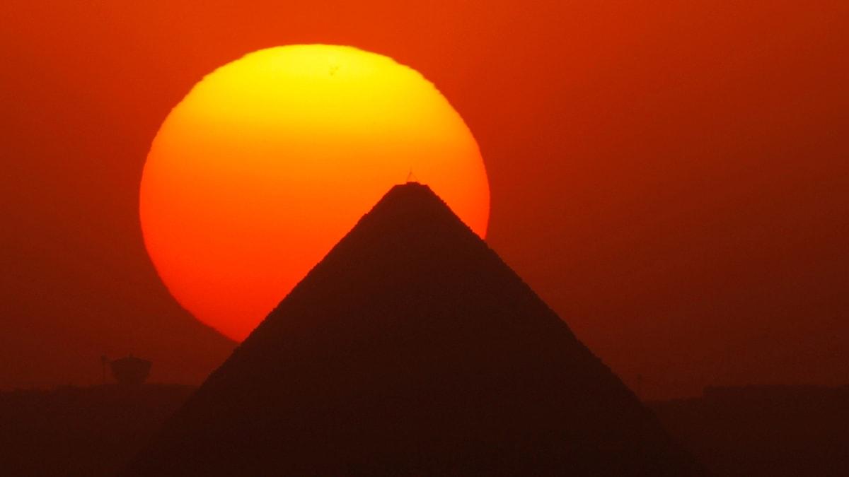 Toppen av en pyramid sticker upp som en siluett i den nedgående solen som står lågt på himlen.