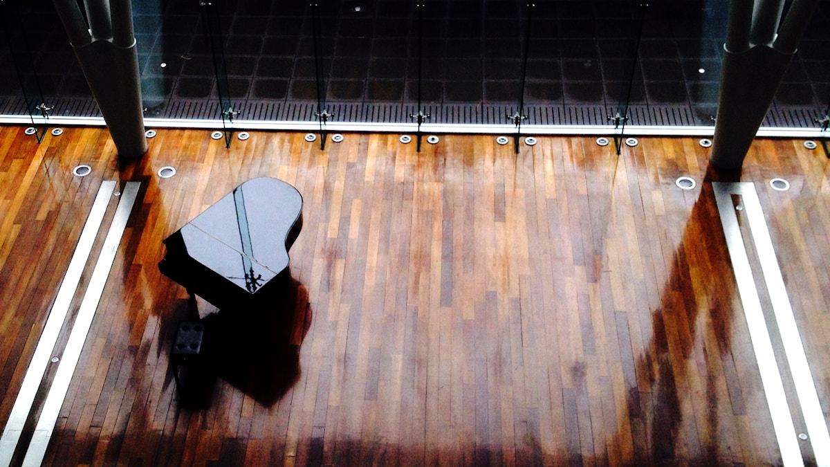Ett ensamt piano på ett ödsligt trägolv.