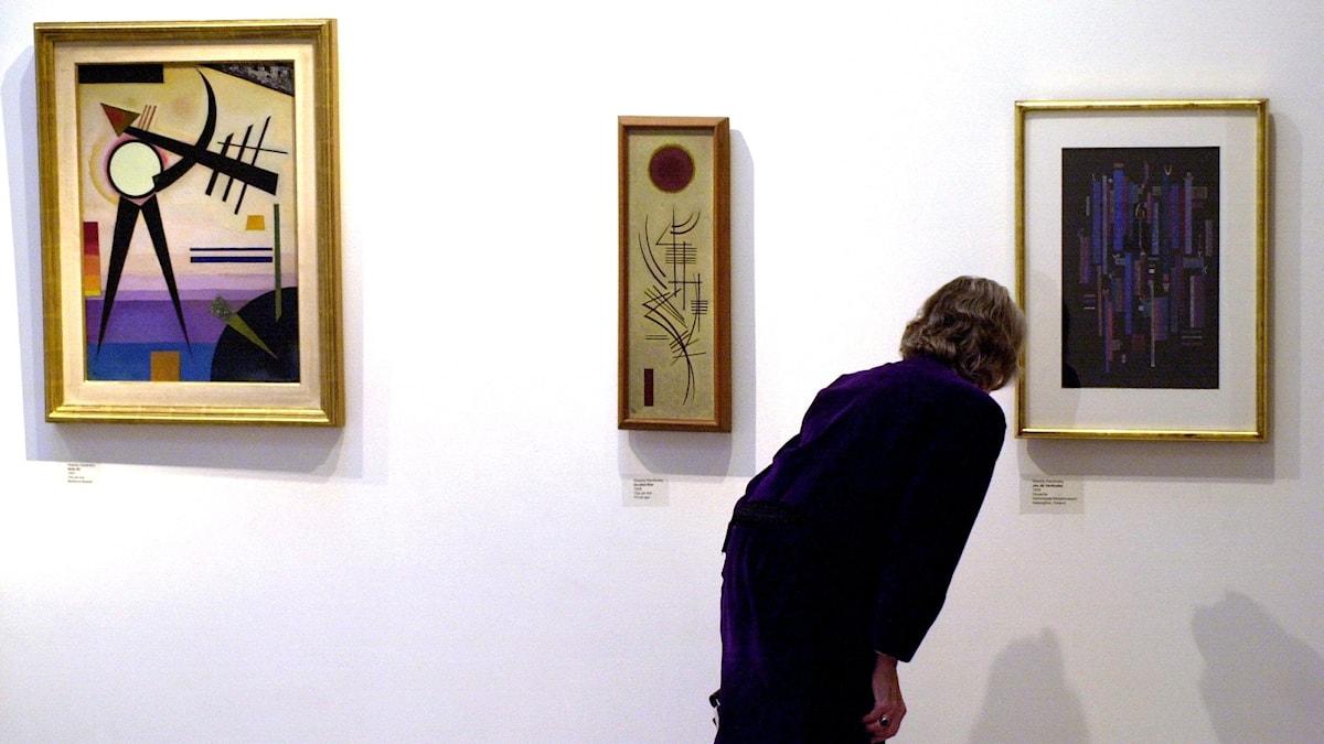 Besökare på ett galleri böjer sig fram och närstuderar en tavla.